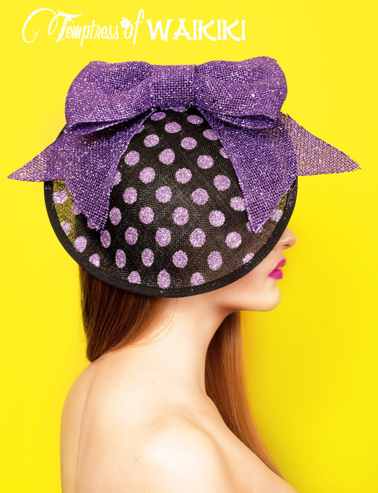 One of a kind giant purple bow hat is a black sinamay hat base decorated with light purple glitter polka dots and a giant glittered purple bow.