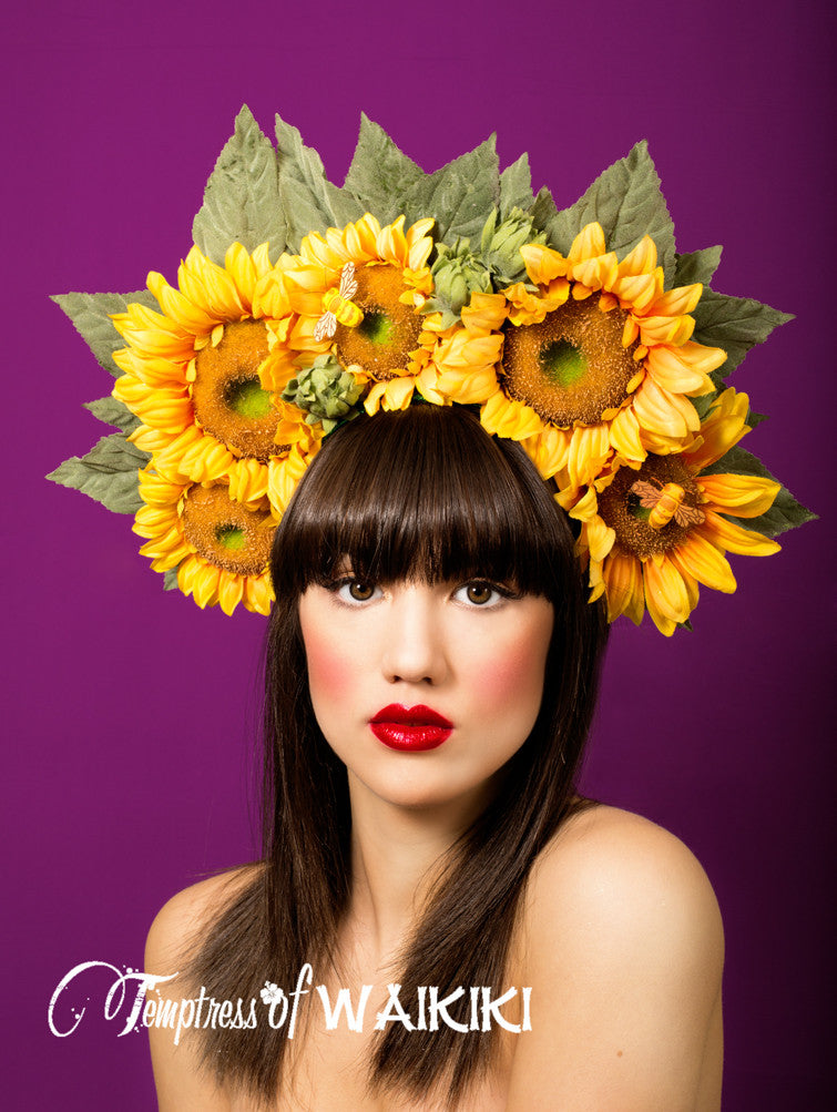 This summery sunflower headdress features large sunflowers decorated with pretty leaves and a bee. Set on a headband. This giant sunflower headdress could be worn to Royal Ascot, a summer wedding or music festival.