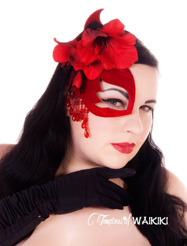 A red velvet half mask fascinator decorated with red flowers, black lace and dripping in red fringe beading. Attaches with a comb, and adjustable hat elastic.    Hand blocked millinery felt backed satin fabric back for your comfort when wearing it.  This decadent half mask is perfect for a masquerade ball, prom, burlesque showgirl or even a fetish club!