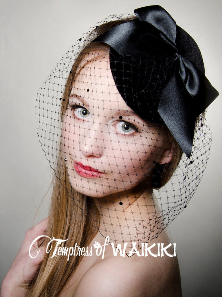 Black vintage inspired velvet covered fascinator base decorated with a large black bow, black veiling, sprinkled in black crystals. Backed with satin, attaches with a comb and hat elastic. This is a classic design which you will get a lot repeated wear out of.