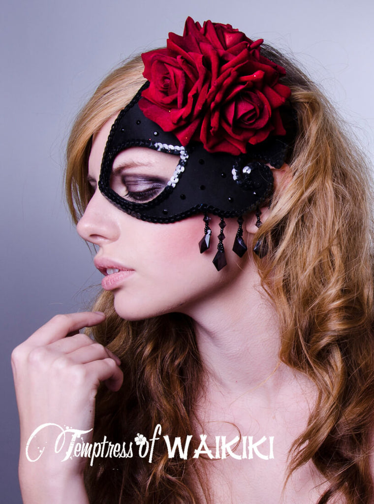 Black satin covered half mask fascinator, decorated with scarlet red velvet roses, edged in sequins, sprinkled in black crystals and featuring a classical black fringe beading. Hand blocked millinery felt backed with satin fabric back for your comfort when wearing it. Attaches with a comb and adjustable hat elastic. The mask is ideal for a masquerade ball, prom, burlesque showgirl or fetish event.