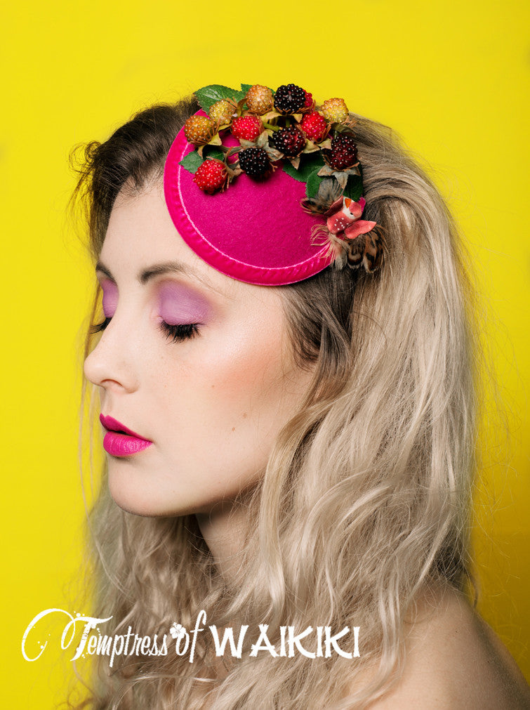 A fuchsia pink fascinator edged in velvet ribbon, decorated with artificial raspberries and a little bird.