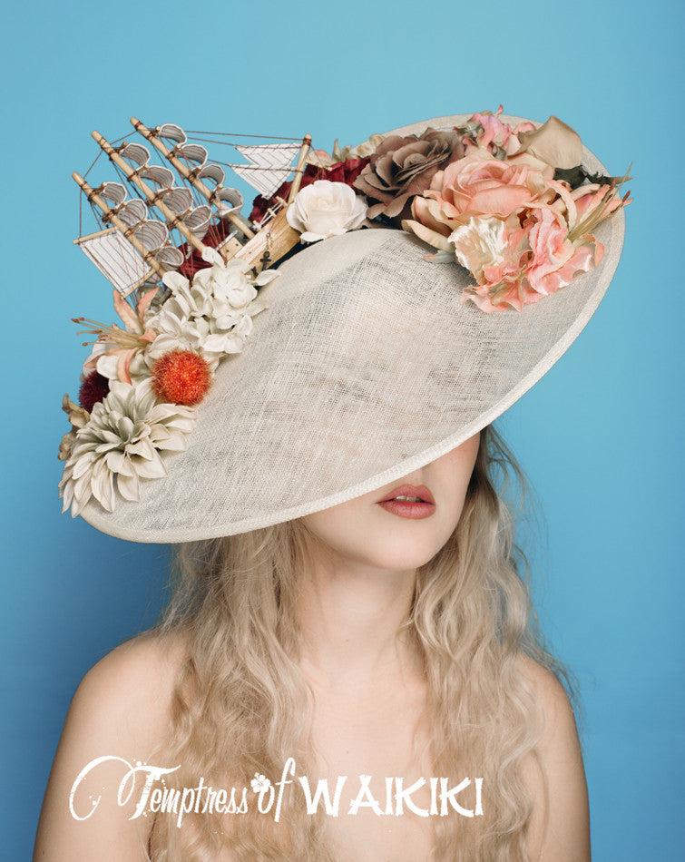 One of a kind ivory sinamay hat, featuring a ship and a sea of flowers in natural tones. Perfect hat for Ladies Day at Royal Ascot, set on a metallic gold headband.