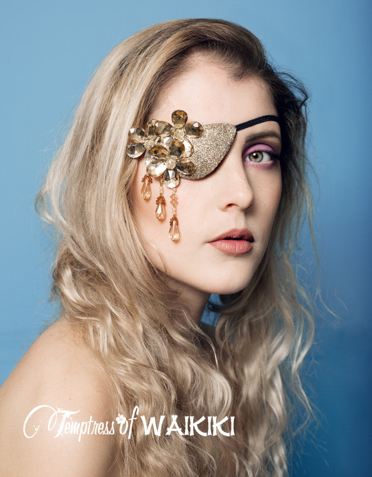 gold glitter eye patch, featuring flower shaped jewels set on a glittering eye patch, dripping with golden coloured beading.