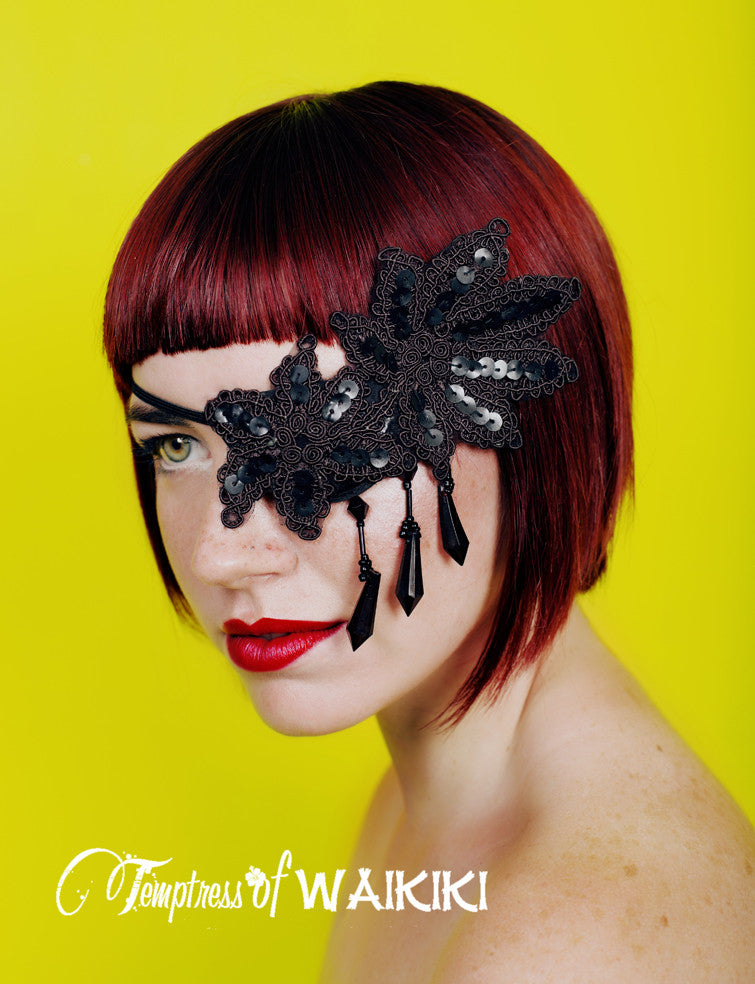 The Gotham black lace eye patch is decadent in sequins, in a classical flower style shape, dripping with black fringe beading.  This lace eye patch is made using a molded eye patch base for your comfort when wearing it. These eyepatches are beautiful fashion statements