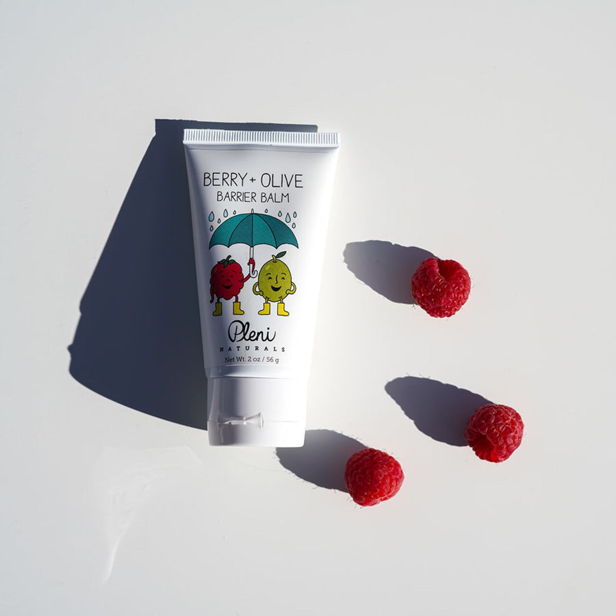 berry olive barrier balm with a white background and a few red raspberries in the photo as their is red raspberry seed oil in the product which is high in omega 3 essential fatty acids and vitamin E