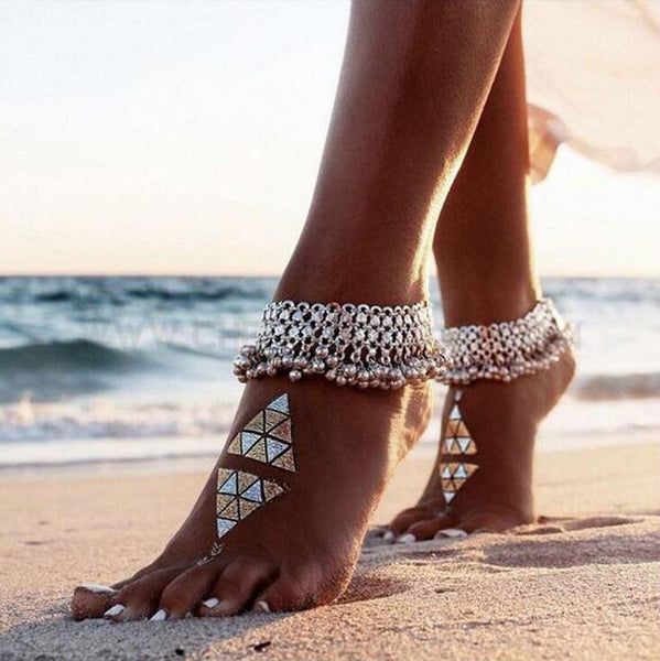 Sexy silver anklet chain on models feet on beach