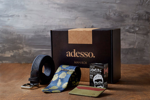 a subscription box featuring a men's tie, belt, and locally made soap bar