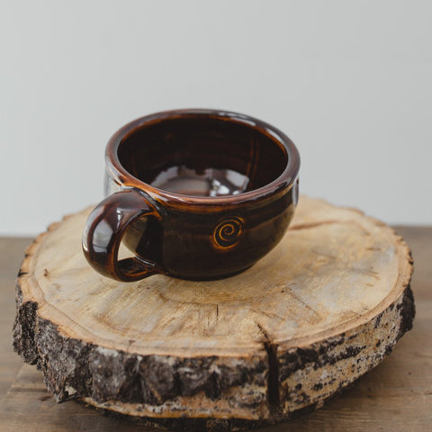a handmade lather mug sits on top of a circular piece of wood