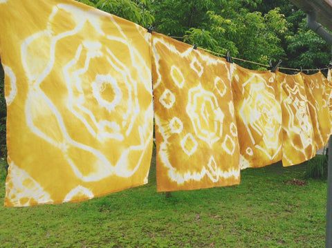 Naturally dyed, yellow dish towels hang on a clothing line outside
