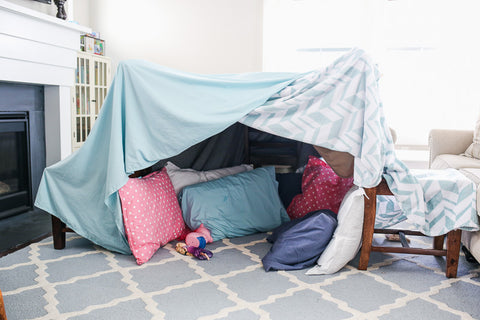 A children's fort made out of blankets and pillows in a living room