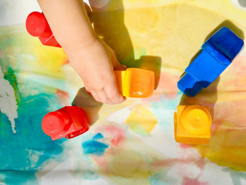 a child painting with ice-cube paint blocks
