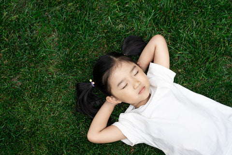 a small girl is laying on a patch of lush grass