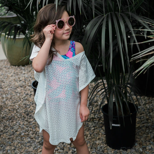 Trendy girl in white cover up and tropical pink swimsuit by Mini Street