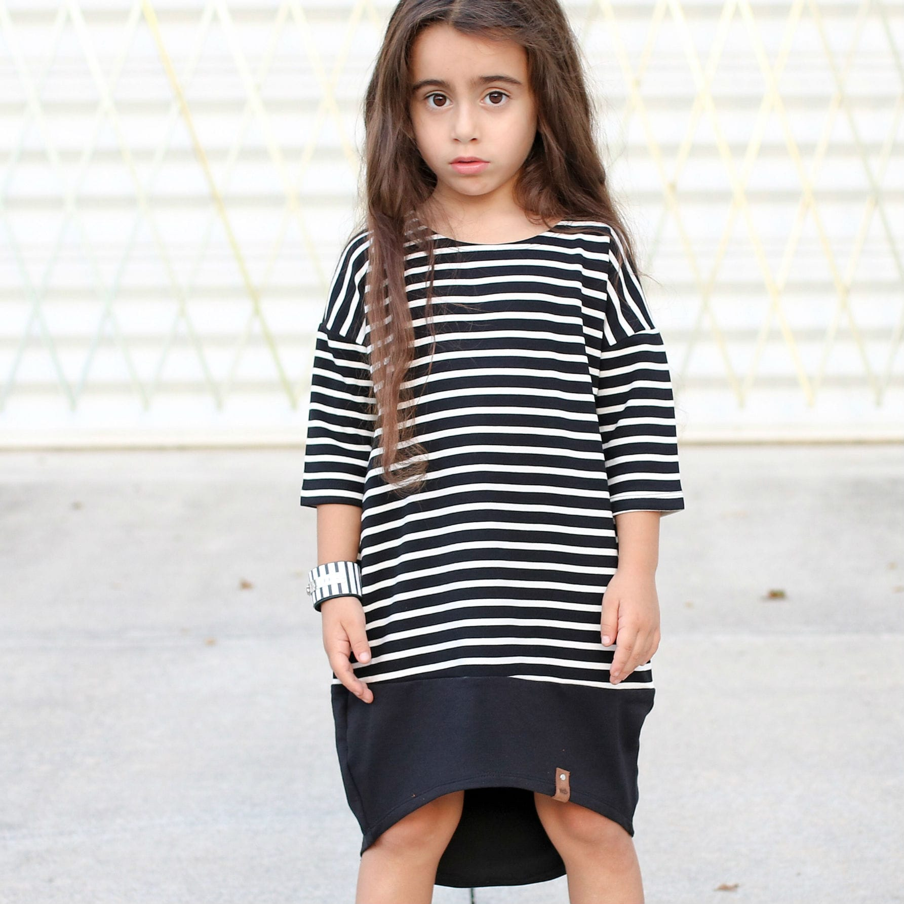 Trendy dressed girl in black and white striped dress by Mini Street