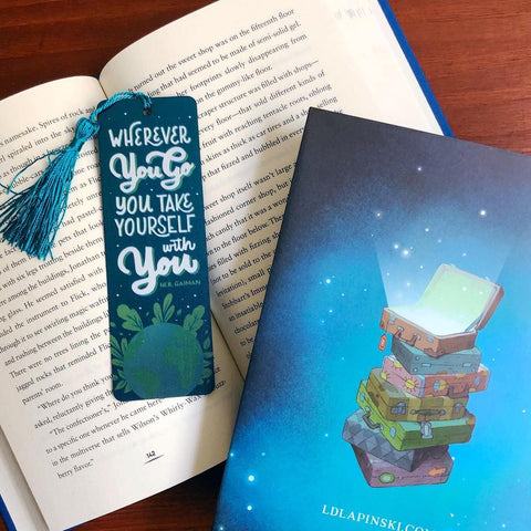 Bookmark reads Wherever you go you take yourself with you -Neil Gaiman. Bookmark image shows the globe with plants wrapping around. Bookmark sits on an open book beside the back cover of another book, showing four suitcases stacked on top of one another.