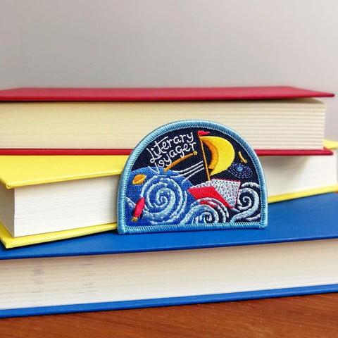 Merit badge reads Literary Voyager, showing a sailboat made out of a book sailing across space. Badge rests on 3 books, each coloured red, yellow, and blue.