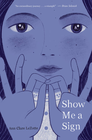 Book cover of Show Me a Sign, showing the face of a young girl holding her hands up in sign.