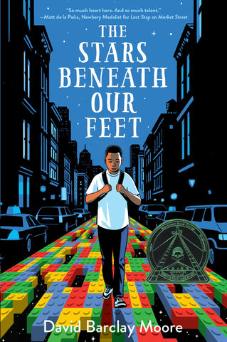 Text reads The Stars Beneath Our Feet by David Barclay Moore. Image shows a young boy walking on a road made of Legos, city buildings on either side. Text is over a light blue background. A CORETTA SCOTT KING medal is printed on cover.