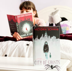 In the forefront is the book City of Ghosts' along with a toy spider. In the background, a young white girl reads the book 'Tunnel of Bones' on a bed.