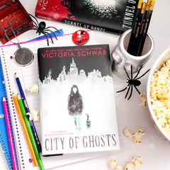 The book 'City of Bones' lies flat on a stack of open notebooks. Surrounding it are pens, a mirror pendant, toy spiders, a button pin, a stack of books, and a bowl of popcorn.