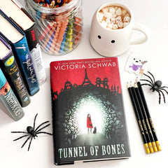 Flat lay showing Tunnel of Bones, surrounded by pencils, books, a mug of hot chocolate, and toy spiders.