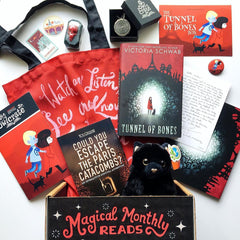 Unboxing photo, showing the book Tunnel of Bones, a choose-your-own-adventure style book, a red tote bag with a quote in white, a black cat stuffie, a mirror pendant necklace in a box, stickers featuring imagery of Paris and Edinburgh respectively, and an author letter.