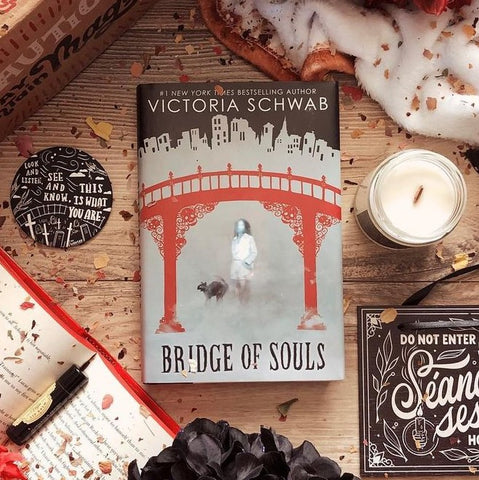 OwlCrate Jr alt cover of Bridge of Souls by Victoria Schwab, showing a ghostly girl and black cut in silver fog, standing underneath a red bridge. Fog turns into city scape above bridge. Book is surrounded by a pocket mirror, candle, and flower petals.