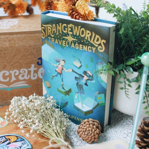 Image shows an OwlCrate Jr exclusive copy of Strangeworlds Travel Agency by L.D. Lapinski. Book image shows a girl being lead by a boy from open suitcase to open suitcase. The boy is holding a bowler hat on his head. Colours are deep to lighter blue. Book is surrounded by an OwlCrate Jr box, a pen with a planet cap, flowers, and an acorn.