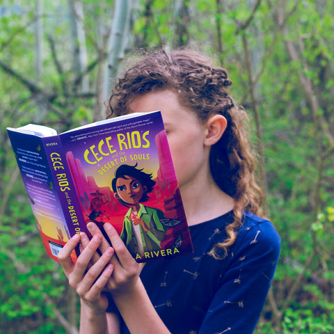 Photo shows girl reading OwlCrate Jr copy of Cece Rios and the Desert of Souls. Girl is standing in green forest.
