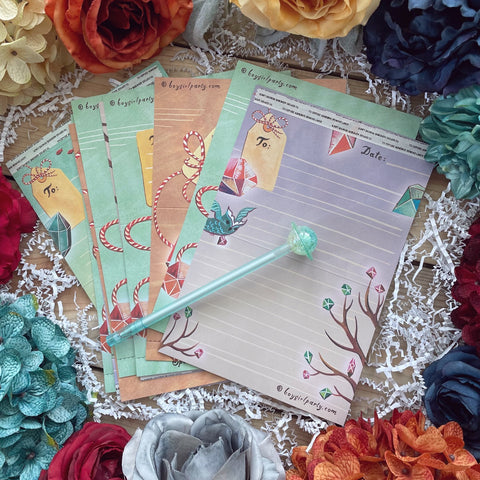Flaty lay of various colourful paper with designs. A blue pen with a planet topper lays on top. Items are surrounded by flowers.