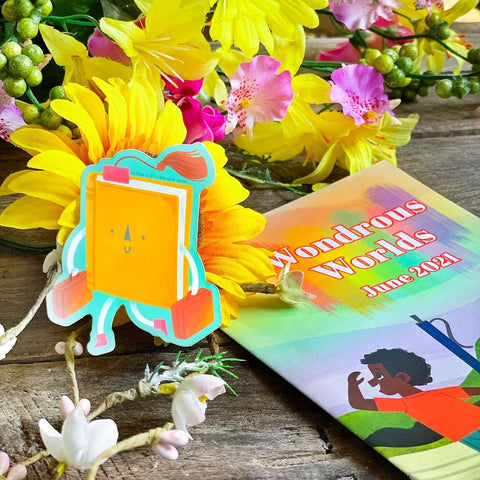 Sticker image is of a book with a smiling face, walking off with suitcases in both hands. Magazine in background, along with bright yellow and pink flowers.