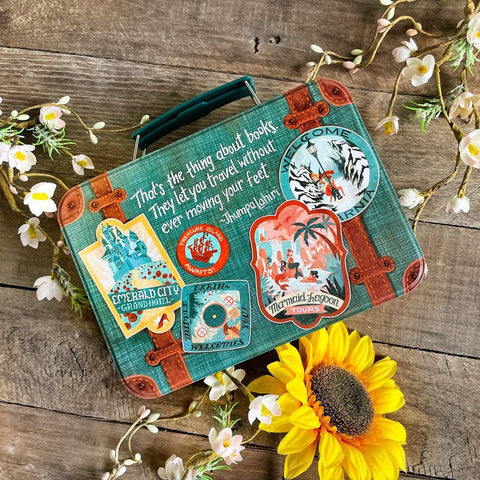 Flat lay photo of tin suitcase with a quote from Jhumpa Lahiri. Tin resembles a travel suitcase, with stickers that show off various worlds.