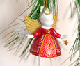Christmas bell angel ornament hung from a tree branch