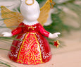 Detail of red and gold dress painted on angel figurine