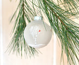 Hand painted white birch trees and cardinals on a frosted glass ornament