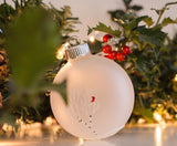 A festive holiday mantel decorated with hand painted white birch ornaments with tiny cardinals