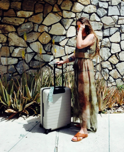 Emily Katz in Palm Springs with her Away Luggage and macrame luggage adornment for when we can travel again.