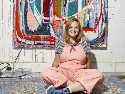 Trish Andersen Fiber Artist in pink jumpsuit in front of fiber carpet painting