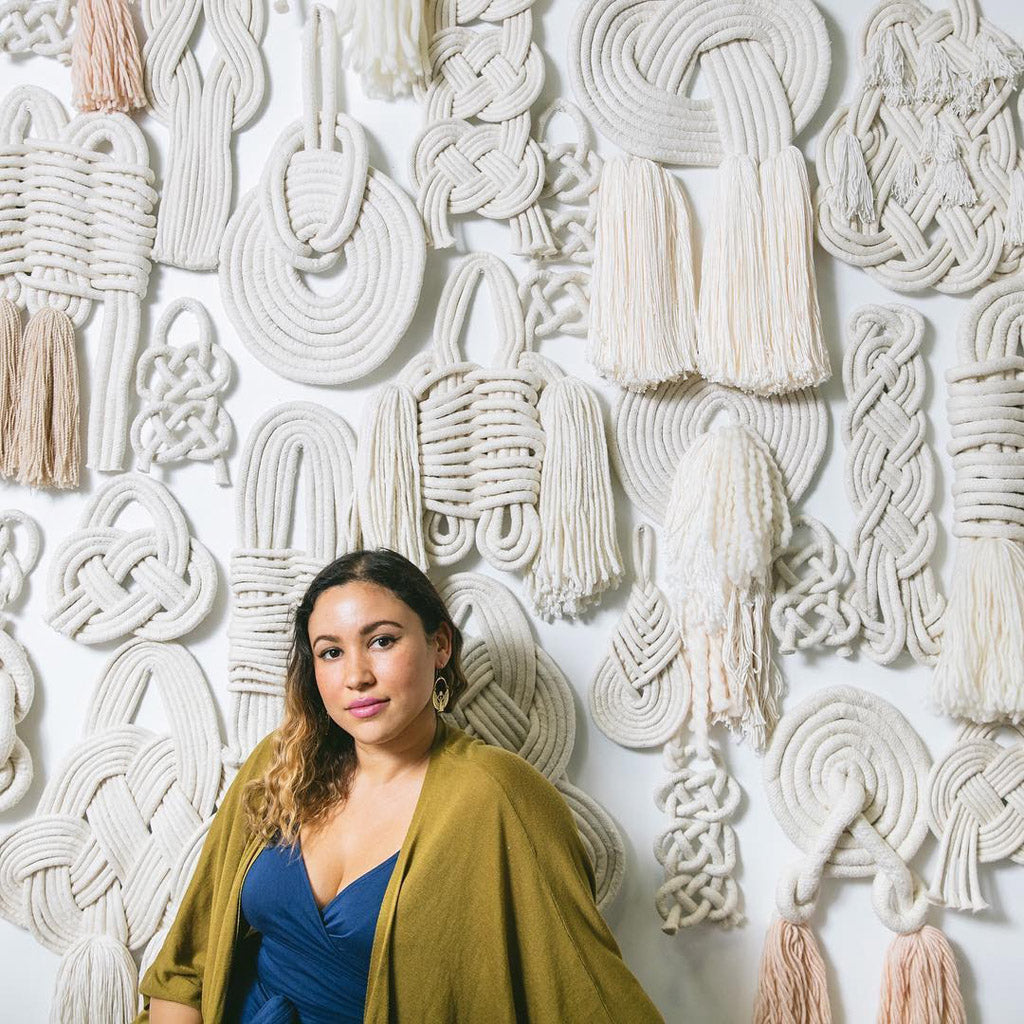 Lise Silva Gomes with a wall of her custom knots