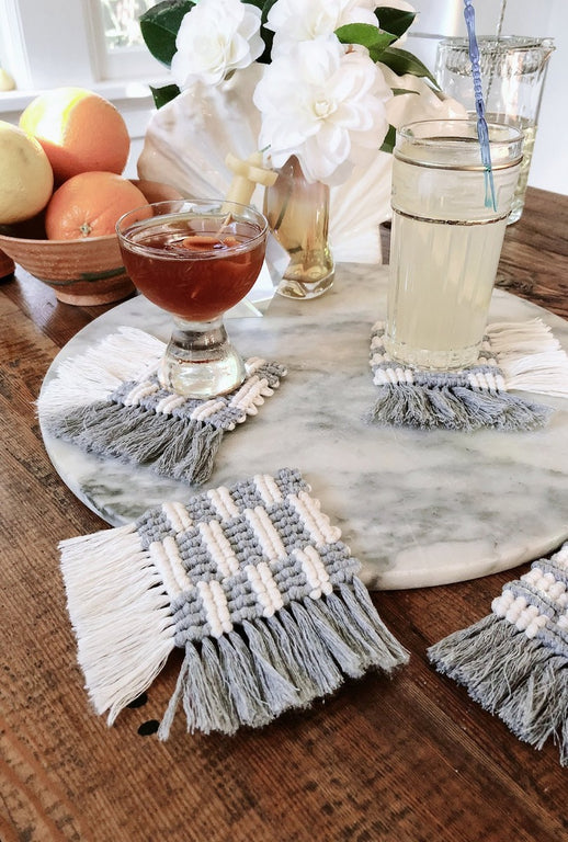 set of 4 diy macramé coasters made with 2mm string on a table with fruit, flowers & cocktails