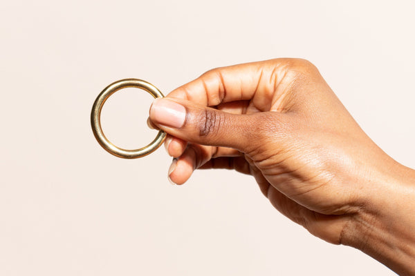 Brass ring in dark skinned woman's hand