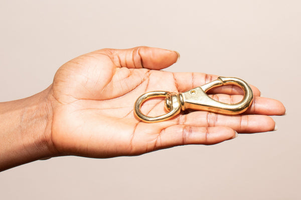 hand holding our brass swivel clip