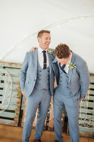 Three piece grey suit and blue tie