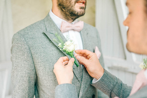 Grey suit and pink bow tie and matching pocket square wedding day suit