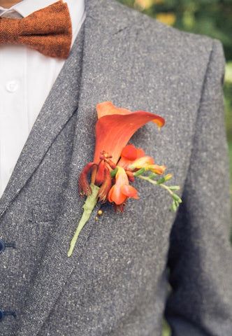 Mens same sex wedding tweed suit, burnt orange bow tie and button hole.  Alternative groom outfit