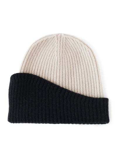 A classic beanie reshaped into a fresh asymmetrical form with a colour block design. Ivory and black colour.