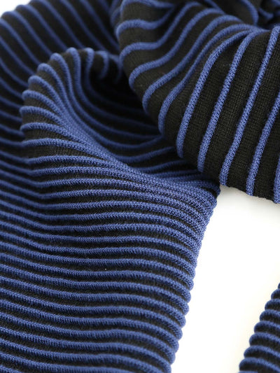 Our soft merino wool scarf has a unique texture with a gradient of knitted ribs. Detail of a black and blue knitted scarf.