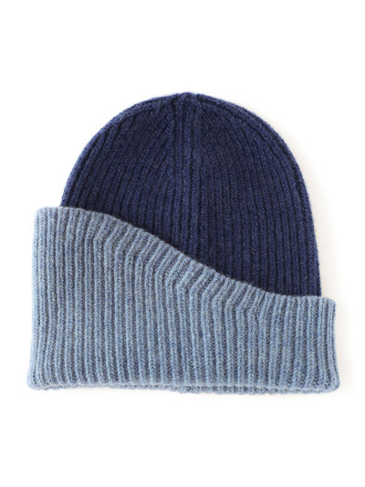 A classic beanie reshaped into a fresh asymmetrical form with a colour block design. Denim and Navy colour.