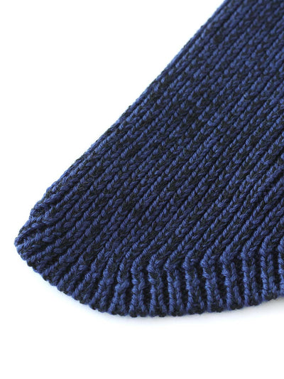 A classic beanie reshaped into a new asymmetrical form, knitted with two colours in premium merino wool. Black and navy colour.